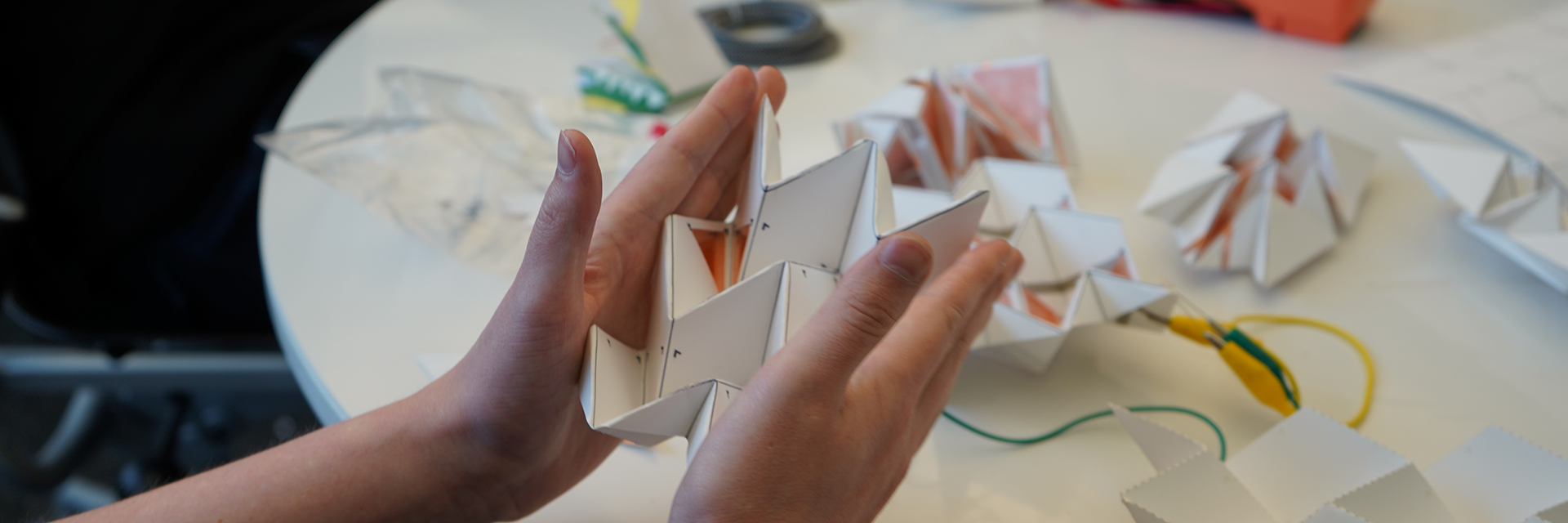Hands squeezing power generating origami.